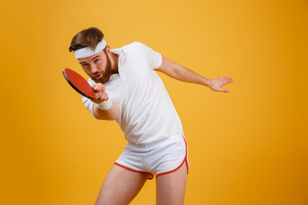 Sportsmand joven hermoso que sostiene la raqueta para el tenis de mesa.
