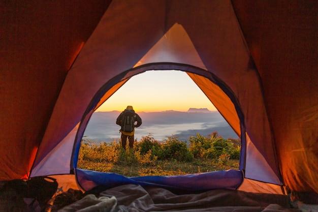 Stand de excursionista en el camping cerca de la carpa naranja y mochila en las montañas