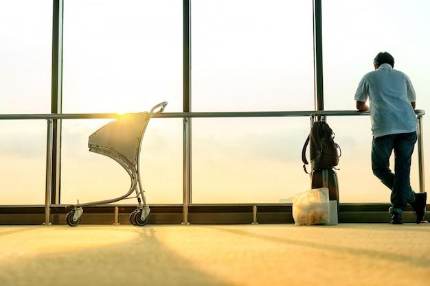 Stand de pasajeros cerca de la ventana para aviones de vuelo antes de la salida.