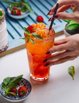 Starberry y jugo de naranja con partículas de hielo, fresa y naranja