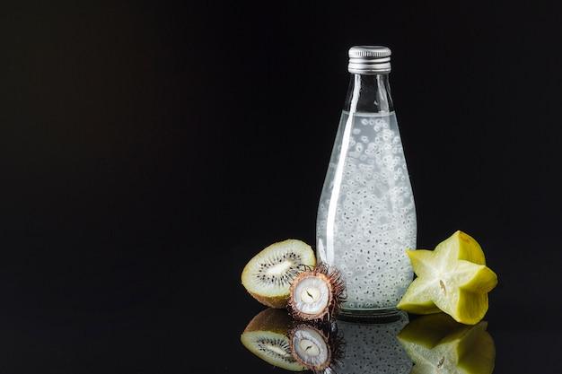 Starfruit y jugo de kiwi sobre fondo negro