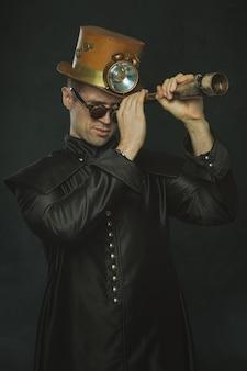 Steampunk hombre con un abrigo largo mirando a través de un telescopio.