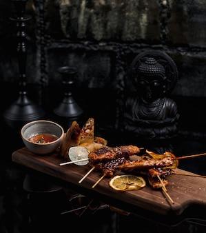 Stick kebab finamente cocido y servido con salsa de naranja