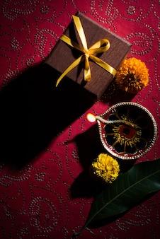 Stock photo de hermoso diwali diya con regalos y flores, sobre fondo decorativo, iluminación cambiante y enfoque selectivo