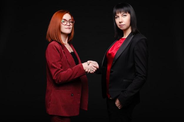 Stock photo retrato de dos mujeres de negocios exitosas en elegantes trajes dándose la mano haciendo un trato. mirando a la cámara, aislar en negro.