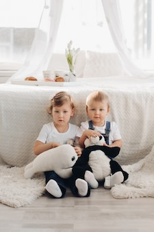Stock photo retrato de dos niños encantadores sentados en el suelo con dos juguetes de peluche en las manos