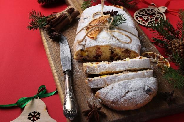 Stollen sabroso de navidad con frutos secos, bayas y nueces sobre fondo rojo. delicias tradicionales alemanas.