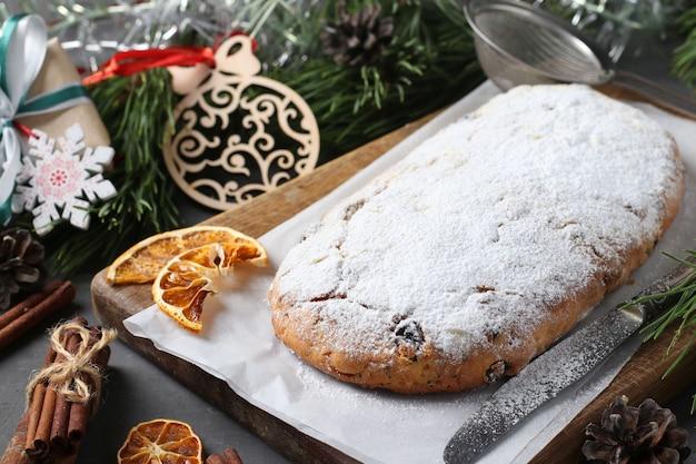 Stollen sabroso de navidad con frutos secos, bayas y nueces sobre tabla de madera. delicias tradicionales alemanas. de cerca