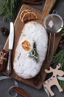 Stollen sabroso de navidad con frutos secos, bayas y nueces sobre tabla de madera. delicias tradicionales alemanas. vista superior