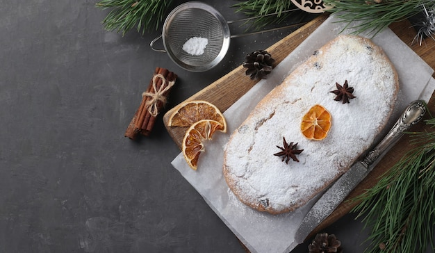 Stollen sabroso de navidad con frutos secos, bayas y nueces sobre tabla de madera. delicias tradicionales alemanas.