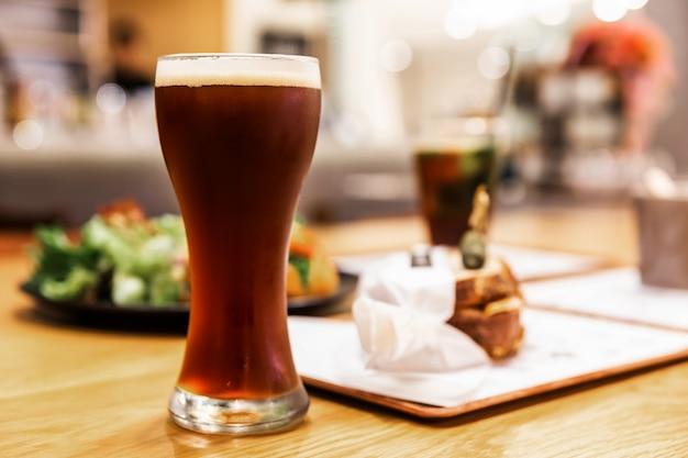 Stout (cerveza negra) con espuma en vaso en una mesa de madera con desenfoque de alimentos