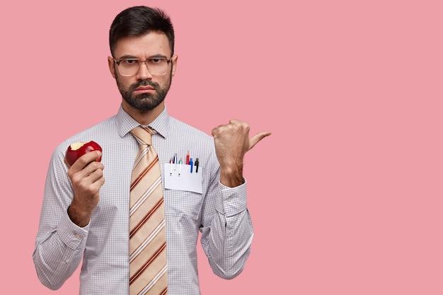 Strern serio jefe usa anteojos de lentes gruesos, come deliciosa manzana, vestido con camisa formal