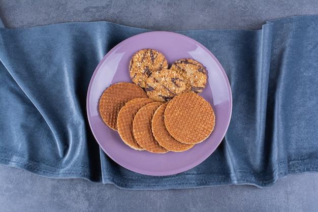 Stroopwafels aislado en una placa violeta sobre una piedra.