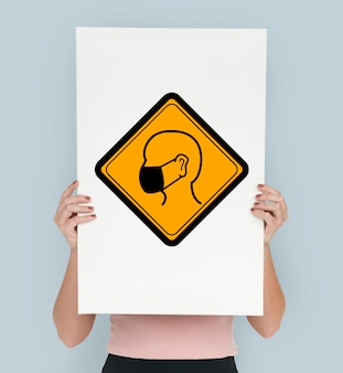 Studio shoot holding banner con señal de atención de máscara de protección