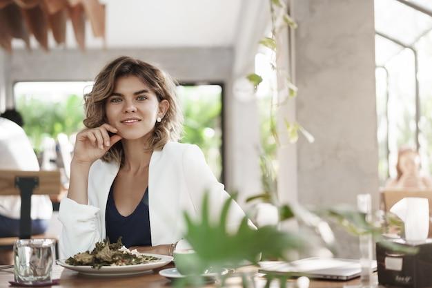 Stylush exitoso ambicioso atractivo joven especialista en marketing sentarse restaurante café moderno comer ensalada saludable beber café sonriente reunión de negocios encantada durante el almuerzo, discutir el trabajo.