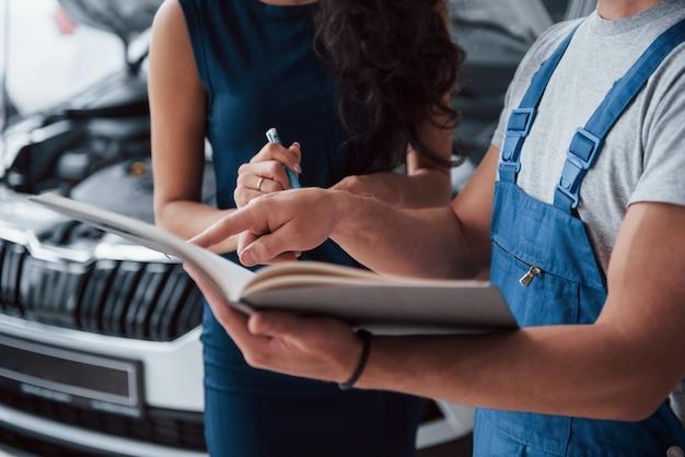 Su firma por favor. mujer en el salón del automóvil con empleado en uniforme azul tomando su auto reparado