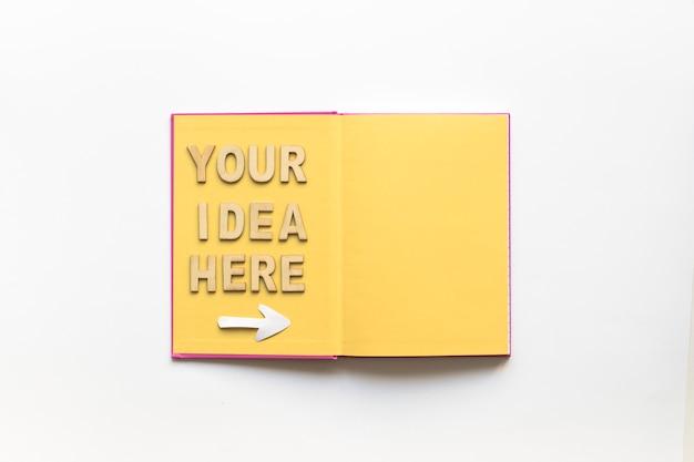 Su idea aquí texto con el símbolo de flecha en el cuaderno