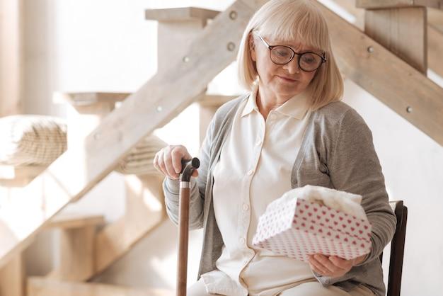 Su presente. agradable mujer mayor deprimida sentada en la silla y mirando la caja de regalo mientras sostiene un bastón