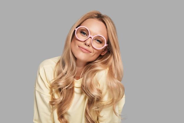 Con su propio estilo. hermosa mujer joven en gafas rosa mirando a la cámara y sonriendo mientras está de pie contra el fondo gris