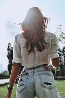 Con su propio estilo. vista trasera de la mujer joven manteniendo la lavanda en el bolsillo trasero de sus jeans mientras está de pie al aire libre
