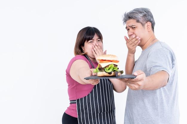 Suave borrosa de pareja asiática obesos muestran signos de hamburguesa de rechazo