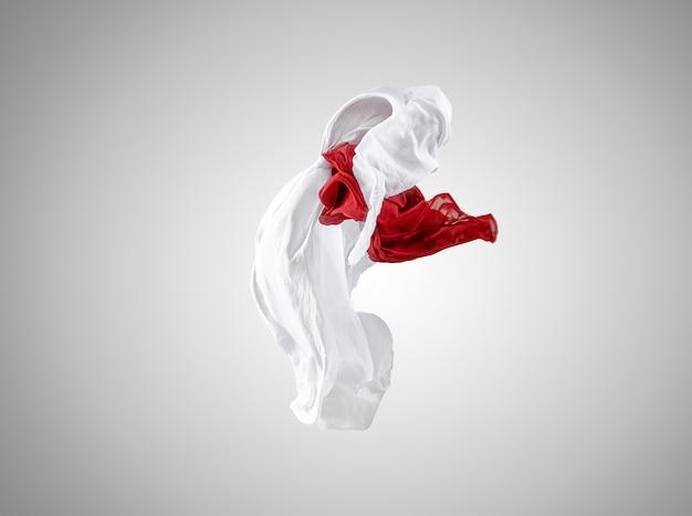 Suave y elegante tela roja y blanca transparente separada sobre fondo gris.