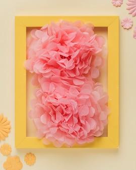 Suave flor falsa y marco de borde amarillo de madera sobre fondo beige