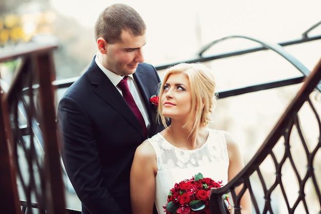 Suave hermosa novia y el novio tomados de la mano mirando el uno al otro cerca de la valla balcón lviv