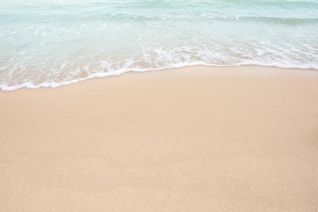 Suave ola de mar en la playa de arena vacía