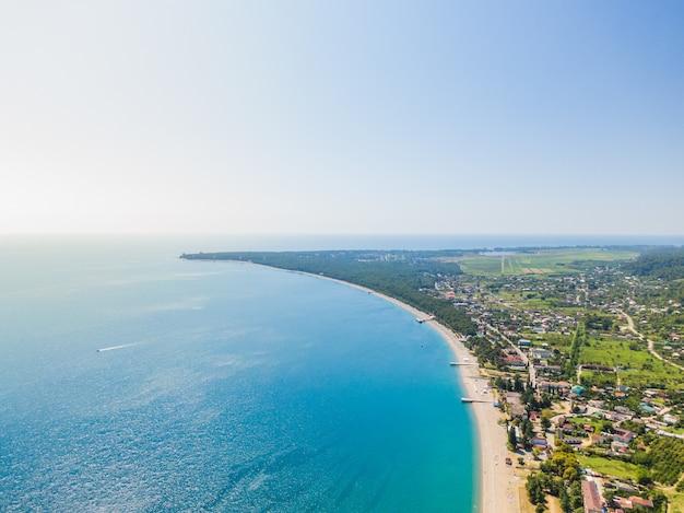 Suave ola de océano azul en la playa de arena