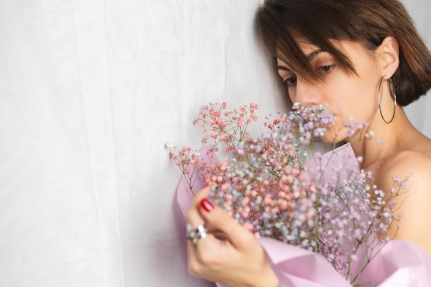Suave retrato de una mujer joven en un trapo blanco en topless sosteniendo un ramo de flores secas multicolores y sonriendo lindo, anticipación de la primavera