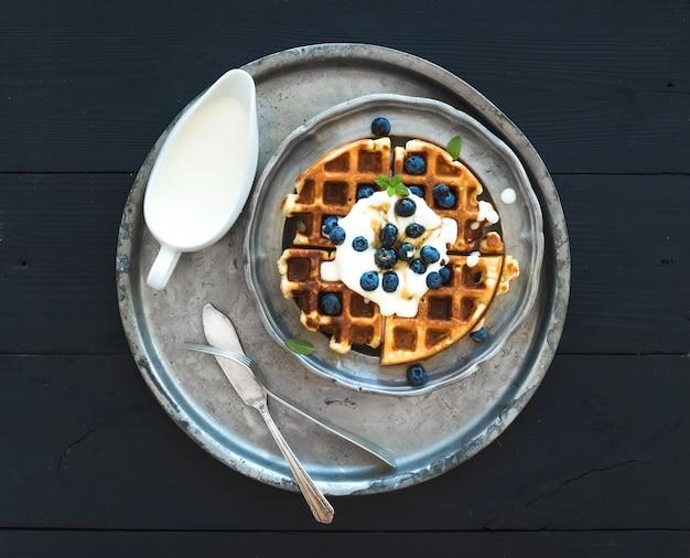 Suaves gofres belgas con arándanos, miel y crema batida en placa de metal vintage sobre mesa de madera negra, vista superior.