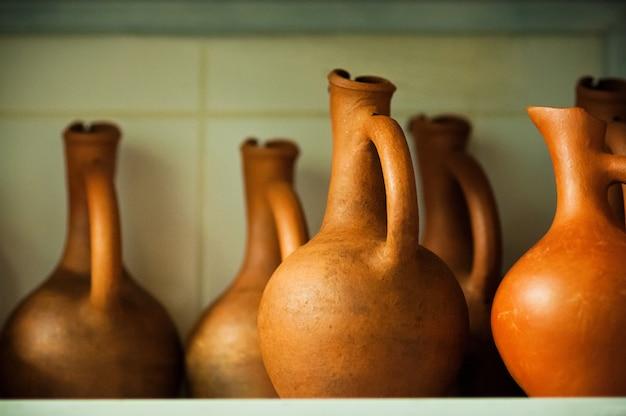 Suaves jarras de vino enfocadas de color terracota en el estante
