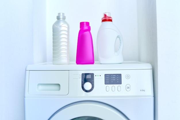 Suavizante de telas y gel de detergente en polvo en la moderna lavadora blanca. productos detergentes