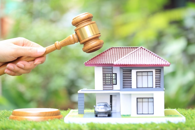 Subasta de propiedades, mano de mujer con martillo de madera y modelo de casa, abogado de bienes raíces y concepto de propiedad de propiedad