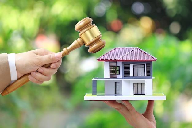 Subasta de propiedades, mano de mujer con mazo de madera y casa modelo en blanco