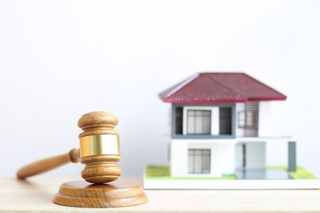 Subasta de propiedades, mazo de madera y casa modelo