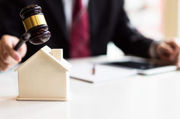 Subastador derribando una casa modelo con su martillo, subasta de venta de propiedades