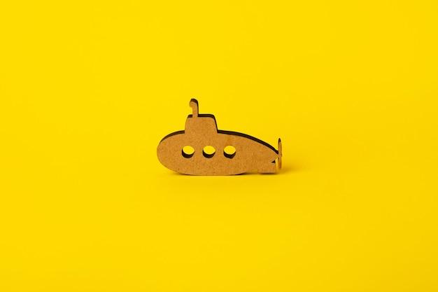 Submarino de madera de juguete sobre fondo amarillo