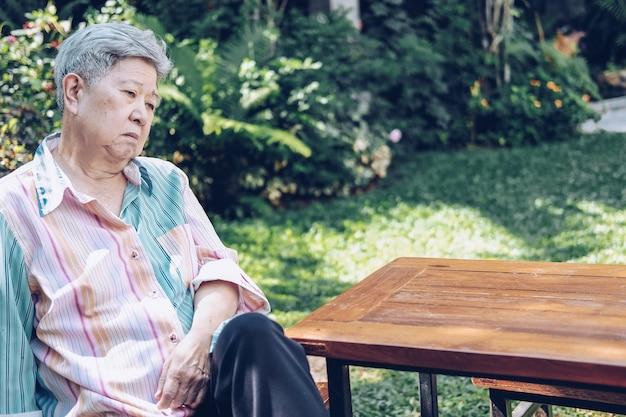 Subrayó deprimido fatigado triste malestar asiático anciano anciano anciano asiático sentado en el jardín.