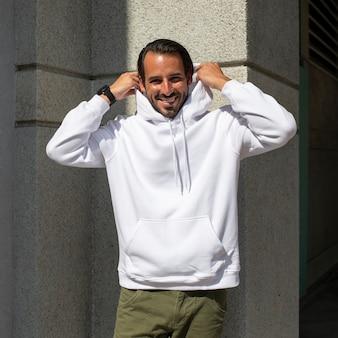 Sudadera blanca en hombre con pantalón verde en la ciudad.
