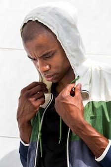 Sudadera con capucha que lleva del atleta de sexo masculino serio que se opone a la pared blanca que mira abajo