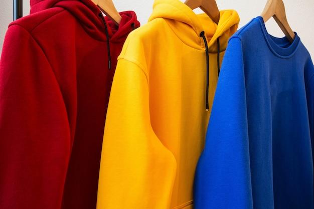 Sudaderas con capucha coloridas en diseño moderno de primer plano de perchas