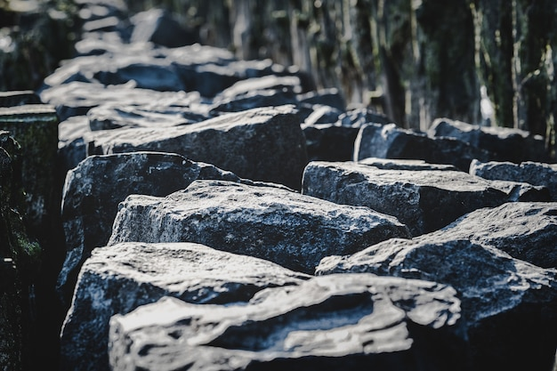 Suelo fangoso de un mar seco y una valla de madera con piedras grandes