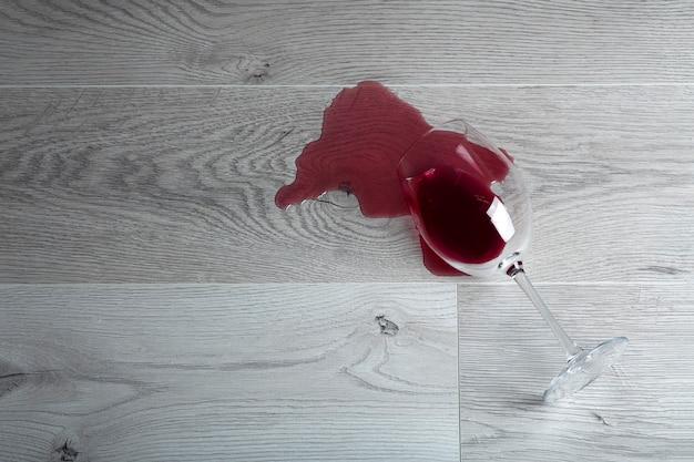 Suelo de madera con copa de vino tinto volcada. vino derramado sobre un piso laminado de madera (parquet) con protección contra la humedad.
