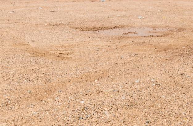 El suelo superficial del primer suelo después de la lluvia con marcas de neumáticos con textura de fondo