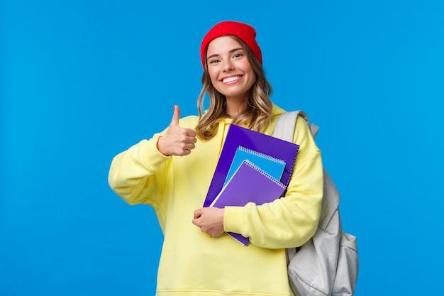 Suena bien alegre, linda e inteligente niña caucásica con gorro rojo que estudia mucho para los exámenes, alienta a los estudiantes a mantenerse al día, muestra el pulgar hacia arriba o con aprobación, sujeta el cuaderno y la mochila
