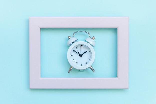 Suena el despertador vintage de doble campana en marco rosa aislado en azul pastel colorido de moda