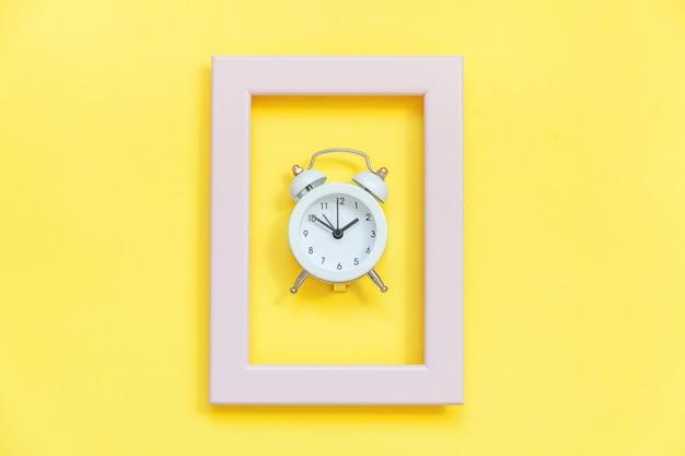 Suena el despertador vintage de doble campana en marco rosa aislado sobre fondo de moda colorido amarillo