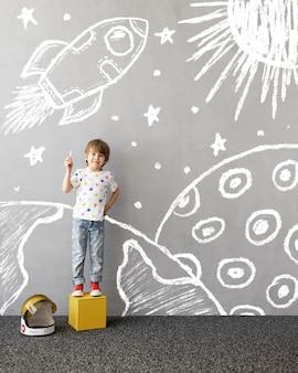 Sueña en grande niño feliz jugando al aire libre niño divertido dibuja un cohete de tiza en la pared